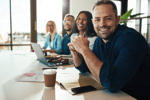 glimlachende-man-op-kantoor-met-collega's