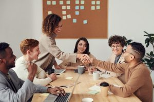 team collega's die elkaar een hand geven met blije gezichten